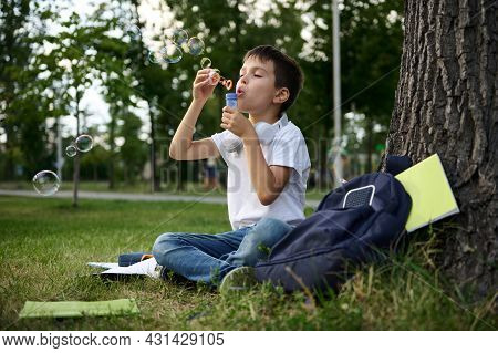 A Handsome Schoolboy Of Elementary Grades Resting In The Park Sitting On The Green Grass After Schoo