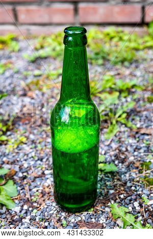 Opened Bottle Of A Beer On The Ground Outdoor