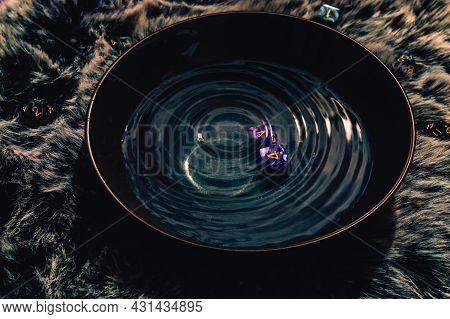 Image Of Two Purple Role-playing Game Dice In A Bowl Filled With Rippling Water Upon A Brown Fur.