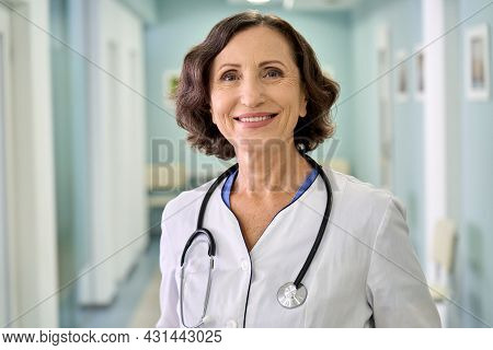 Portrait Of Smiling Older Senior Female Professional Doctor Physician Pediatrician Wearing White Rob