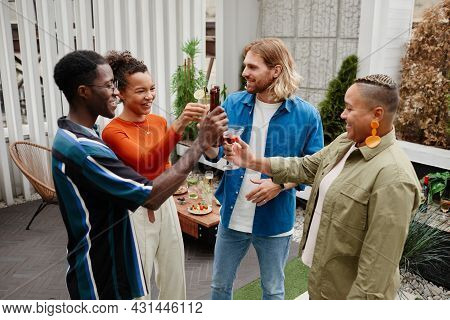 Diverse Group Of Carefree Young People Clinking Drinks While Enjoying Outdoor Party With Friends