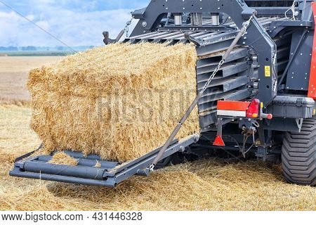 Forming Sheaves Of Straw Into Tight Briquettes On A Powerful Agricultural Tractor Against The Backdr
