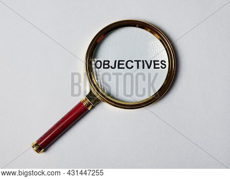Word Objectives Through Magnifier On Blue Gary Background. Target Concept.