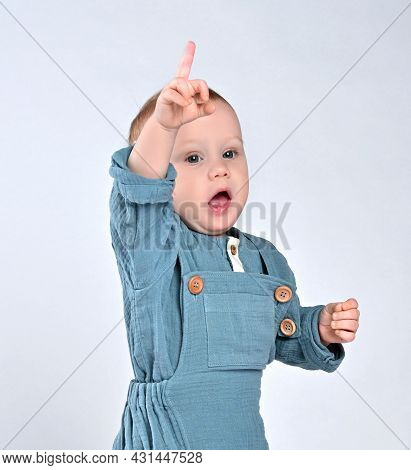 Indignant Todler Todler In A Blue Jumpsuit Raised His Hand With A Middle Finger Up, Calling For The