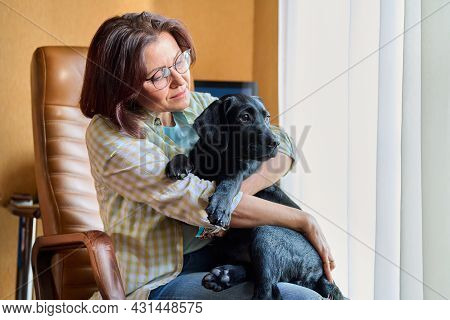 Portrait Of Middle Aged Woman And Black Labrador Puppy Dog
