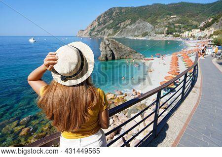 Italian Riviera. Pretty Girl With Hat On Promenade Looking At Monterosso Al Mare Village On Cinque T