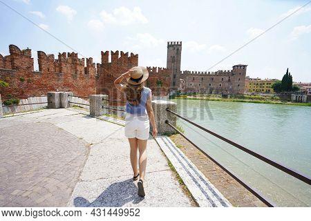 Promenade Riverside In Verona, Italy. Beautiful Lady Walking Along Promenade With Medieval Fortress