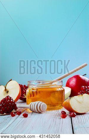 Happy Rosh Hashanah. Jar With Honey, Apples And Pomegranates On A Blue Background. Jewish Traditiona