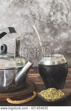 Traditional Argentinian Hot Beverage Called Mate In A Wooden Table