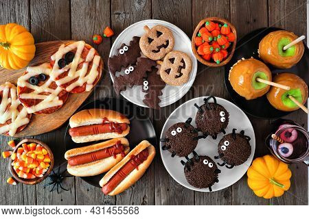 Halloween Party Food Table Scene Over A Rustic Wood Background. Overhead View. Spooky Mummy Pizzas,