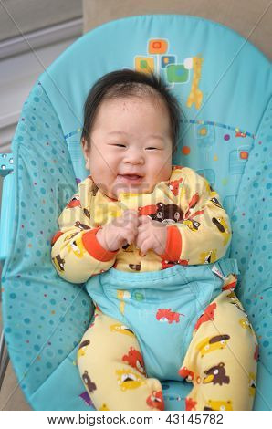 Smiling baby boy on bouncer seat