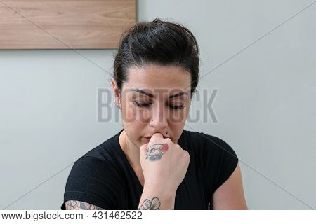 Brazilian Woman, Tattooed, With Her Hand On Her Chin, Showing Concern And Frustration.