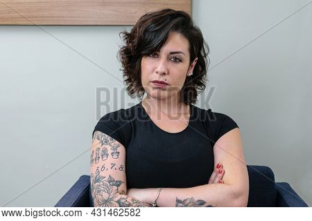 Brazilian Woman, Tattooed, With Arms Crossed And Facing The Camera. Upset And Angry.