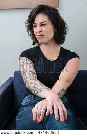 Brazilian Woman, Tattooed, With Her Hands Crossed And Looking To The Side, Showing Contempt.