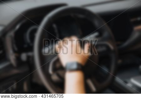 Abstract Blur Hands On The Steering Wheel Of A Car While Driving.