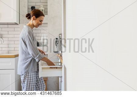 Modern Housewife Tidying Up Kitchen Cupboard During General Cleaning Or Tidying Up