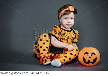 Serious, Little Girl In Halloween Costume With Pumpkin Candy Bowl. Funny Child In The Studio, Grimac