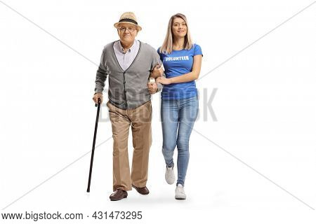 Full length portrait of a female volunteer helping an elderly man walking with a cane isolated on white background