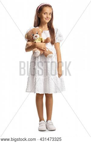 Full length portrait of a girl in a white dress holding a teddy bear isolated on white background