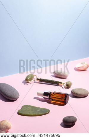 Cosmetic Product In A Glass Bottle With A Pipette And Gua Sha Scraper And Roller. Smooth Stones Near