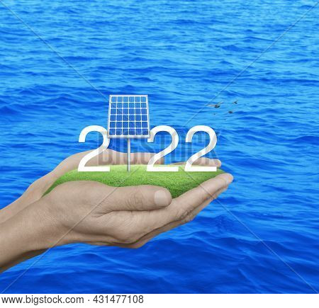 2022 White Text With Solar Cell On Green Grass Field In Man Hands Over Blue Sea With Birds, Happy Ne