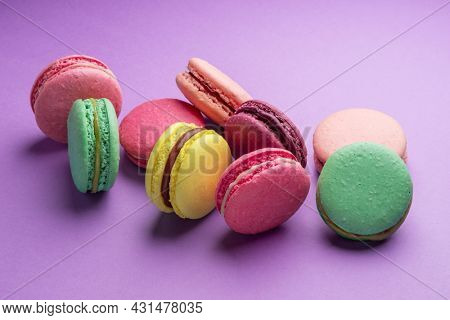 Colorful sweet macarons or macaroons, flavored cookies on purple background.