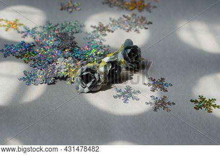 Glittery Snowflakes With Gray Artificial Roses On A Gray Background. A Scattering Of Multicolored Sp