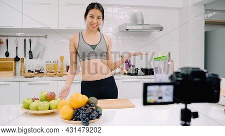 Blogger Sporty Asian Woman Using Camera Recording How To Make Apple Juice Video For Her Subscriber,