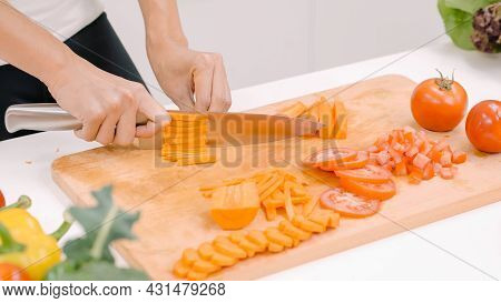 Happy Asian Woman Cut Lots Of Carrot Prepare Ingredient For Making Food In The Kitchen, Female Use O