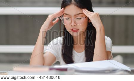 Asian Student Women Read Books In Library At University. Young Undergraduate Girl Stress Tired Have