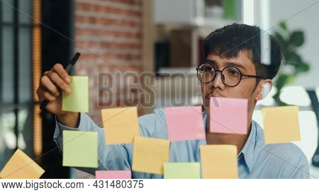 Asian Creative Man Stick A Sticky Note On Glass Board. Young Professional Business Male Write Inform