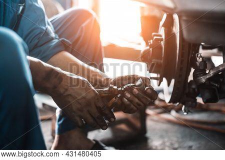 Low Key Young Man Using Tool For Repair Brake Car A Part Of Wheel Tire In Garage.