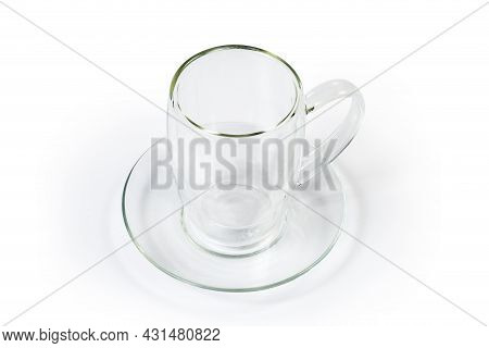 Empty Transparent Glass Cup With Handle And Double-bottomed Hollow On Glass Saucer On A White Backgr