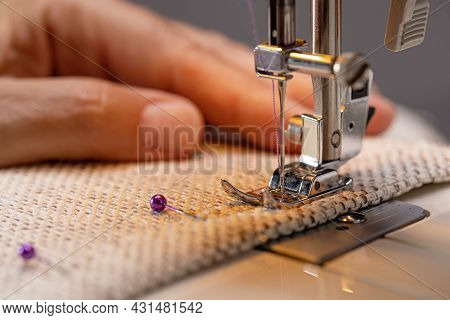 Sewing Machine Foot On Fabric With Needle And Thread Ready To Sew. The Operator's Hand On The Materi