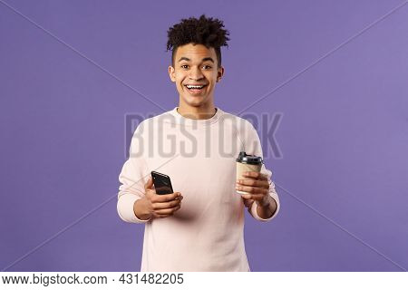 Waist-up Portrait Of Happy Enthusiastic Hispanic Man With Smartphone, Hold Mobile Phone And Drinking