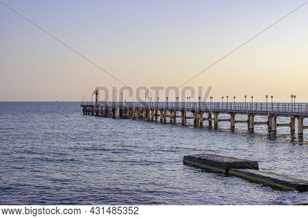 Sea In The Evening. The Pier Goes Off Into The Distance. Dark Blue Sky And Water.concrete Blocks And
