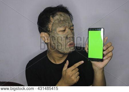 Sad Asian Man Showing Blank Screen When He Use Beauty Face Mask
