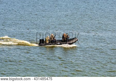 Five Military Men With Weapons And Special Equipment In The Black Motor Boat. Special Operations For