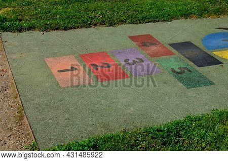 Playground In The Park, Where He Jumps On The Playing Area Of rubber Tiles With Numbers. Around Is