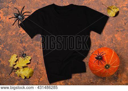 Black T-shirt Mockup. Black T-shirt On Orange-brown Wooden Background With Halloween Decor. T-shirt