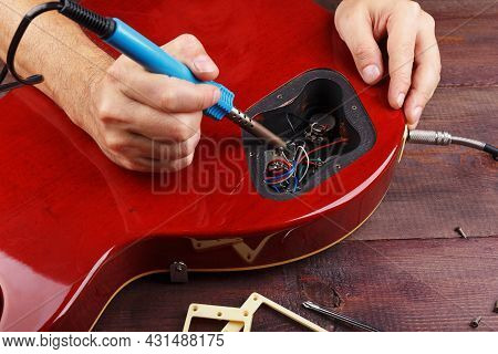 Guitar Technician Soldering Electric Guitar Electronics In His Workplace.