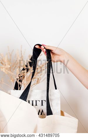 Bag Full Of Magazines And Dry Flowers. Mocap Of Reusable White Cotton Eco-bag On White Insulated Bac