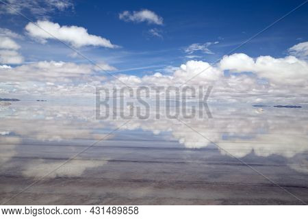 Salar De Uyuni. Salt Flat With Water. Reflections Of A Perfect Sky. Blue Sky And Clouds Reflection O