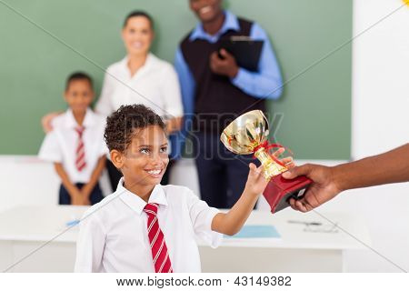 elementary school boy receiving a trophy in classroom with teachers and classmate