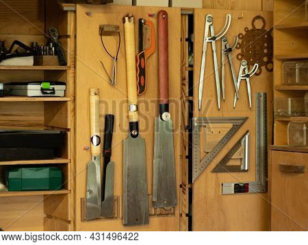 Carpentry Workshop. Metal Compasses, Carpentry Saws, Squares And Other Tools Hang On The Doors Of Wo