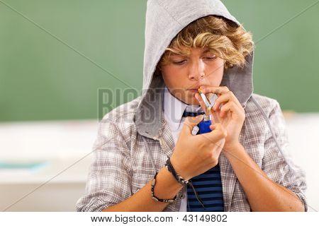 bad high school teen boy lighting cigarette in classroom