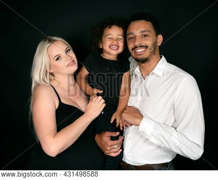 Portrait Of A Stylish And Happy Multi-ethnic Family Expecting A Baby