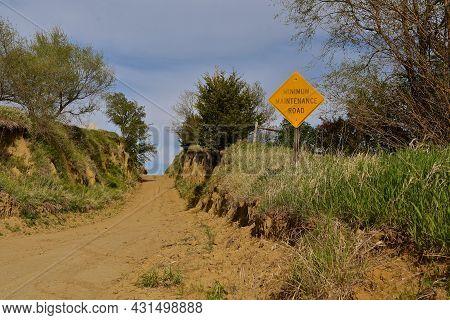 A Dirt And Gravel Minimum Maintenance Road Is Cut Through A An Earthen Bank.