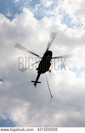 Silhouetted Flying Helicopter With Blurry Moving Propeller And Carrying Sling On Overcast Sky.