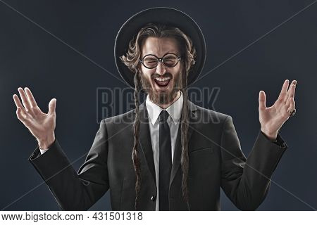 An emotional male Orthodox Jew looks at the camera and is very glad. Studio shot on a dark blue background.